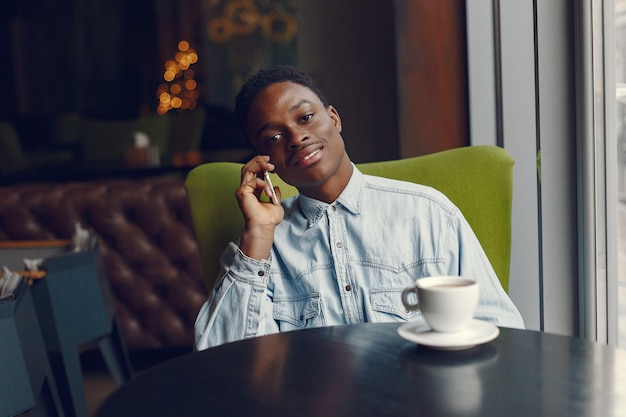 Murzyn siedzi w kawiarni i pije kawę