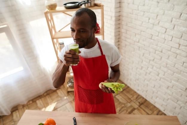 Murzyn w fartuchu pije świeżego soku selerowego w kuchni.