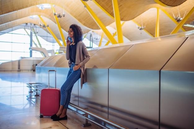 Murzynka czeka jej lot używać telefon komórkowego przy lotniskiem