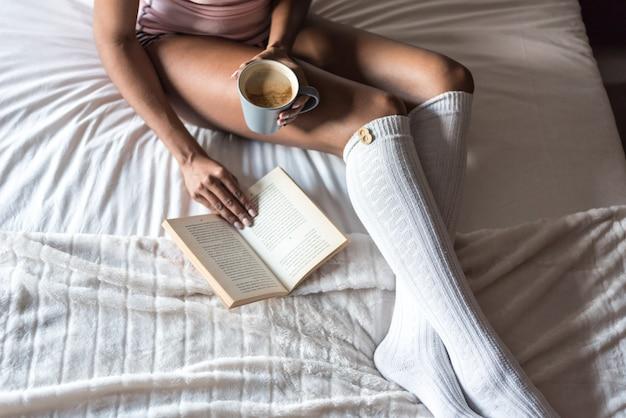 Murzynka czyta książkę i pije kawę na łóżku z skarpetami