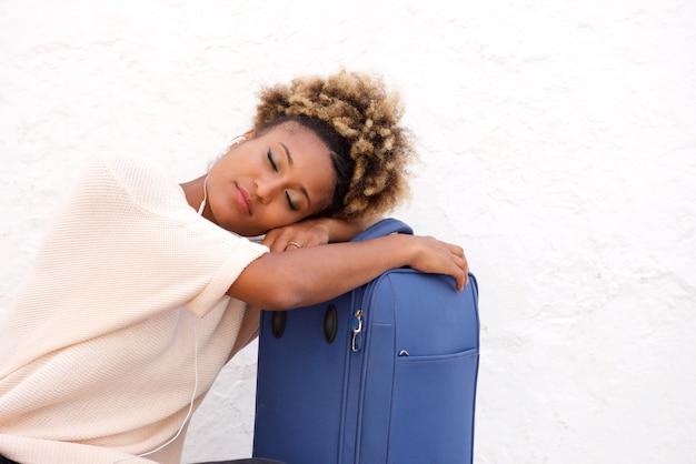 Murzynka podróżnika dosypianie z walizką na chodniczku