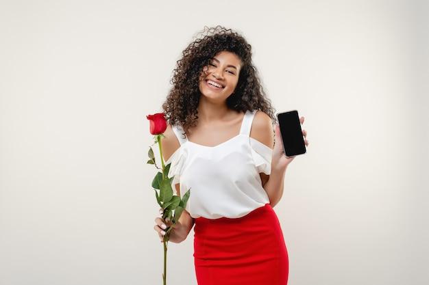 Murzynka pokazuje pustego ekranu telefon z czerwieni różą odizolowywającą