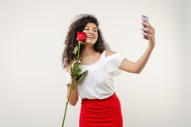 Murzynka robi selfie z różą jest ubranym czerwieni spódnicę i białą bluzkę odizolowywającymi