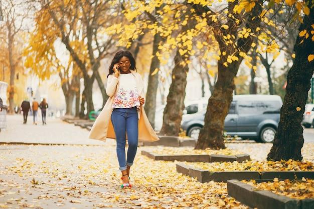 Murzynka stoi w jesieni mieście
