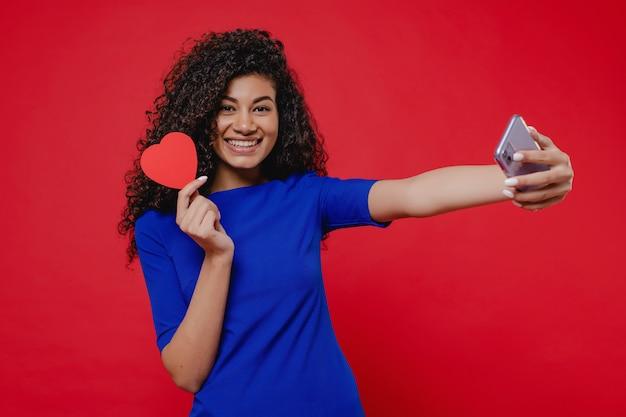 Murzynka uśmiecha się selfie i robi selfie z valentine kartą w kształcie serca na czerwonej ścianie