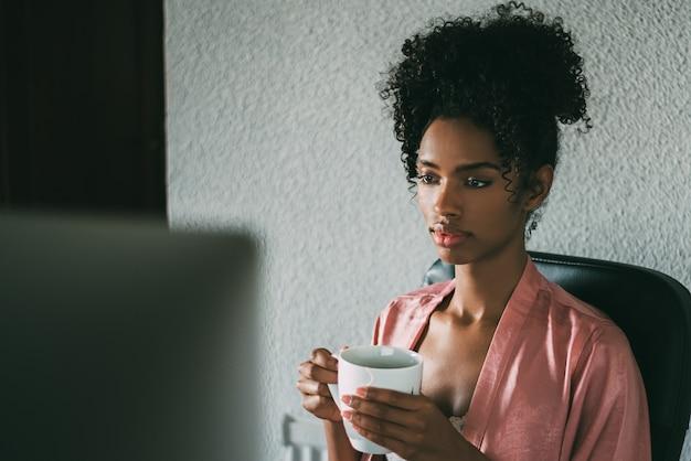 Murzynka w domu pracuje z komputerem i kawą w ranku