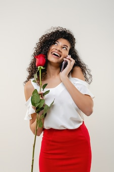 Murzynka z czerwieni różą opowiada na telefonie i ono uśmiecha się odizolowywam