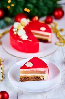 Mus ciasto ciasto boże narodzenie deser pokryty lustrem czerwonym glazury z nowy rok dekoracje na lampy bokeh białe tło, nowoczesne europejskie ciasto boże narodzenie tematu.