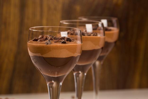 Mus czekoladowy w szklankach na drewnianej powierzchni