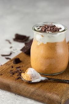 Mus czekoladowy z bitą śmietaną i kawałkami czekolady w szklankach