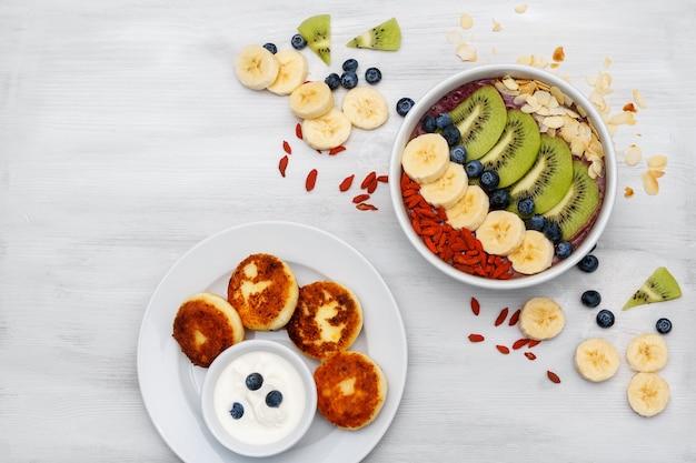 Mus owocowy w miseczkach na zdrowe śniadanie. świeże koktajle organiczne z banana, kiwi, spiruliny, trawy pszenicznej i limonki z jagodami i owocami na białym tle. widok z góry, kopia przestrzeń.
