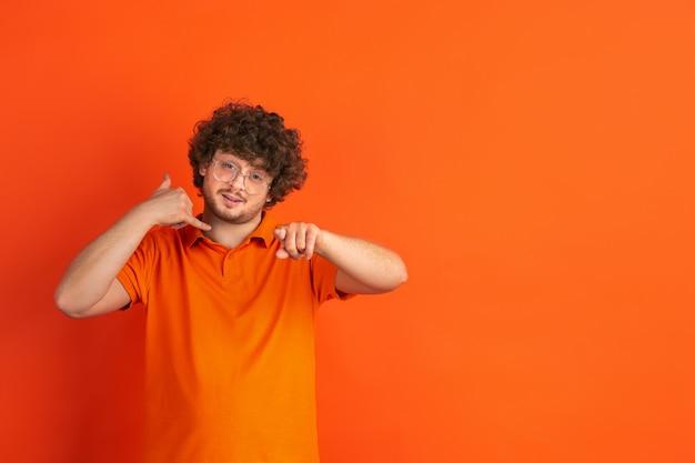 Musisz do mnie zadzwonić. kaukaski monochromatyczny portret młodego człowieka na pomarańczowej ścianie. piękny męski model kręcony w stylu casual.