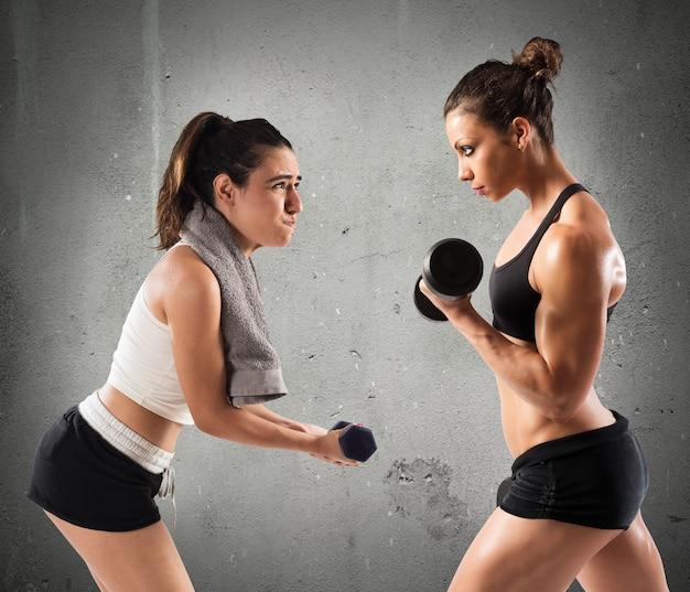 Muskularna dziewczyna trenuje z niezdarną dziewczyną