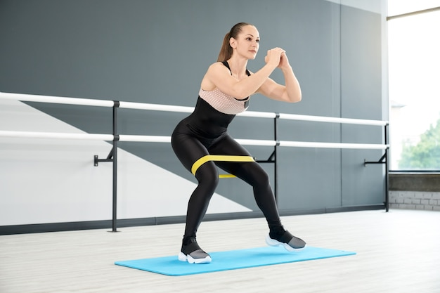 Muskularna kobieta nogi treningu za pomocą zespołu fitness