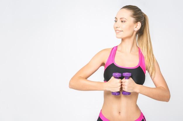 Muskularna kobieta robi ćwiczenia z hantlami na biceps