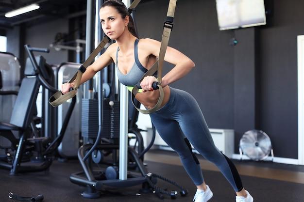 Muskularna kobieta robi pompki treningu ramion z paskami trx fitness w siłowni.