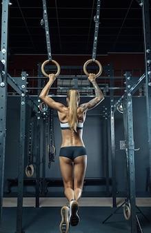 Muskularne plecy dziewczyny sportowiec crossfit w czarnym stroju sportowym wisi na kółkach gimnastycznych