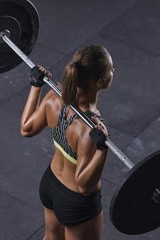Muskularne plecy kobiety podnoszące ciężary w gim