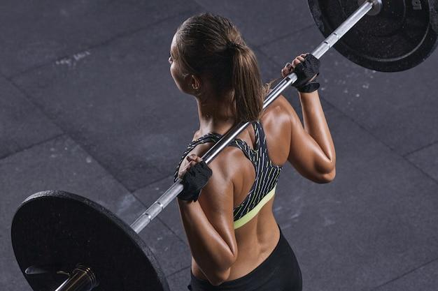 Muskularne plecy kobiety podnoszące ciężary