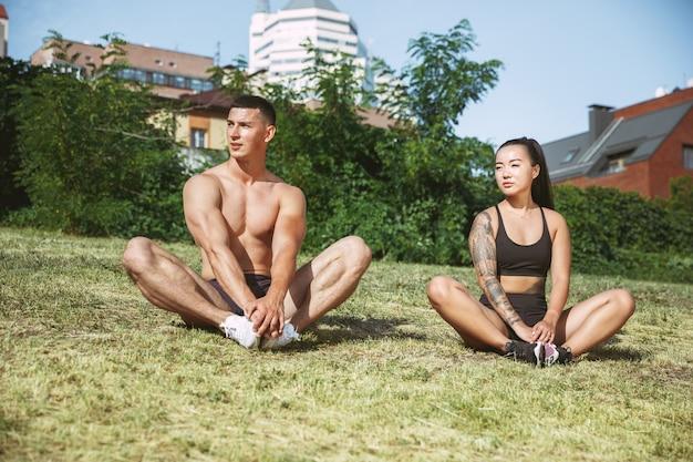 Muskularni sportowcy robią trening w parku. gimnastyka, trening, elastyczność treningu fitness. letnie miasto w słoneczny dzień na tle pola. aktywny i zdrowy tryb życia, młodość, joga, kulturystyka.