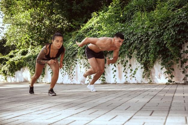 Muskularni sportowcy robią trening w parku. gimnastyka, trening, elastyczność treningu fitness. letnie miasto w słoneczny dzień na tle pola. aktywny i zdrowy tryb życia, młodość, kulturystyka.