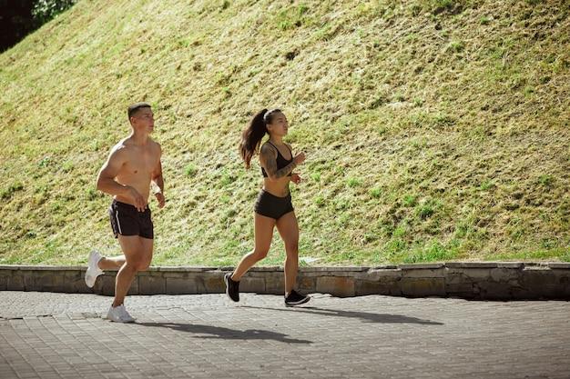 Muskularni sportowcy robią trening w parku. gimnastyka, trening, elastyczność treningu fitness.