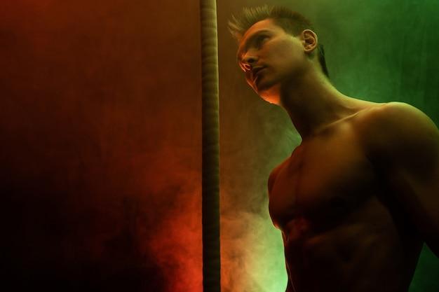 Muskularny artysta cyrkowy z cord lisse na czarnym tle wędzone