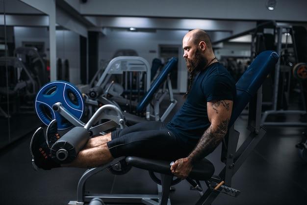 Muskularny atleta trenuje nogi na maszynie do ćwiczeń, trenuje na siłowni. brodaty mężczyzna na treningu w klubie sportowym, zdrowy styl życia