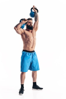 Muskularny, bez koszuli, wytatuowany, brodaty mężczyzna kulturysta sportowiec trening z kettlebell