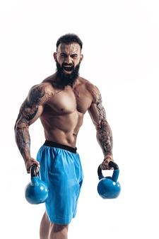Muskularny bez koszuli z wytatuowanym brodaty sportowiec kulturysta treningu z kettlebell na białej ścianie. izolować
