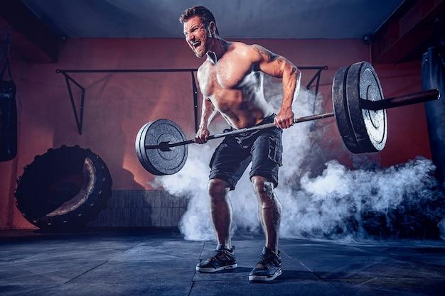 Muskularny brodacz poćwiczyć w siłowni, ćwiczyć, silny męski brzuch nagi tułowia. dym na ścianie