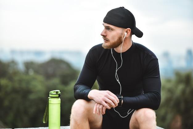Muskularny brodaty sportowiec sprawdzający spalone kalorie na inteligentnym zegarku po dobrej sesji treningowej w parku miejskim.