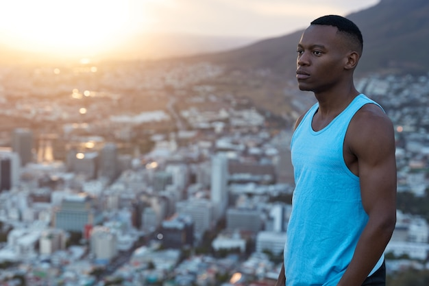 Muskularny, energiczny, przemyślany ciemnoskóry mężczyzna wchodzi na trybunę sportową z profilu, w górach, dużo miejsca na kopię reklamy, informacji lub sloganu