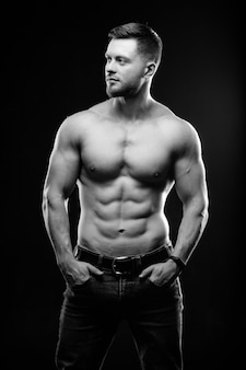 Muskularny facet z nagim torsem pozuje z rękami w kieszeniach. zdjęcie studyjne. portret przystojny mężczyzna w dżinsach na ciemnym tle. czarno-białe zdjęcie. zbliżenie.