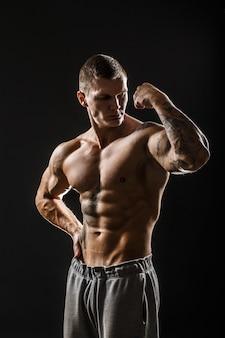 Muskularny facet z tatuażem. pojedynczo na ciemnym tle