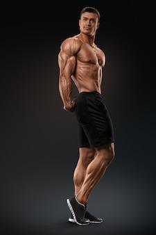 Muskularny i sprawny kulturysta fitness model mężczyzna pozowanie na czarnym tle silny i przystojny ty