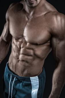Muskularny i sprawny młody kulturysta fitness model męski pozowanie na czarnym tle