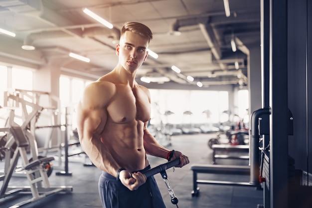 Muskularny kulturysta fitness robi ciężkie ćwiczenia na bicepsy na maszynie z kablem w siłowni