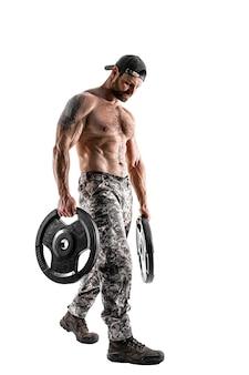 Muskularny kulturysta sportowiec mężczyzna w spodniach kamuflażu z nagim treningiem tułowia z hantlami na białej ścianie. izolować