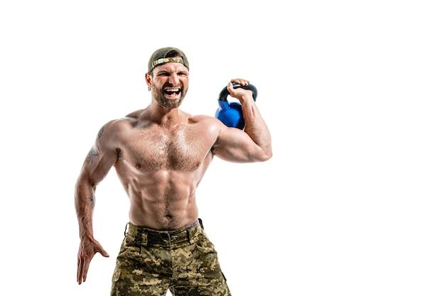 Muskularny kulturysta sportowiec mężczyzna w spodniach kamuflażu z nagim treningiem tułowia z kettlebell na białej ścianie. izolować