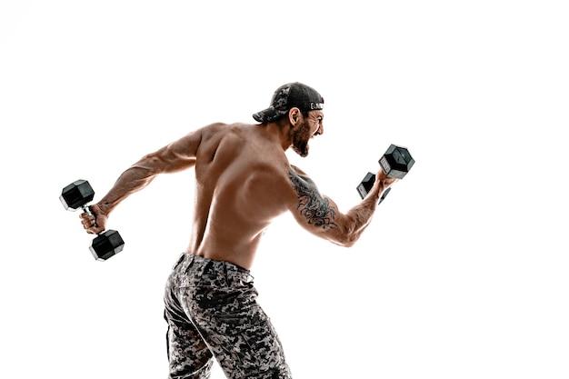 Muskularny kulturysta sportowiec mężczyzna w spodniach kamuflażu z nagim tułowiem uderzającym hantlami jak bokser na białej ścianie.