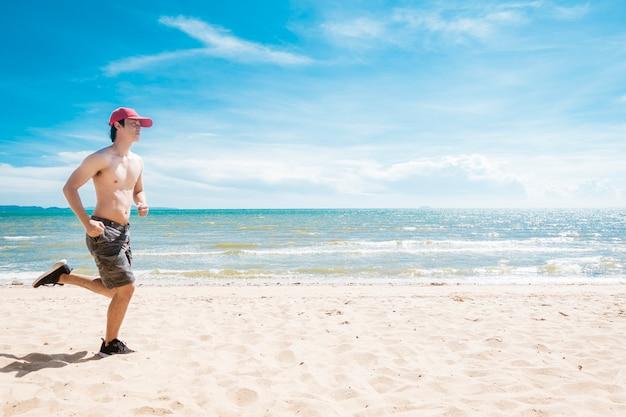 Muskularny mężczyzna biegnie po plaży