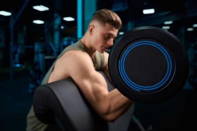 Muskularny mężczyzna budowanie bicepsów ze sztangą.