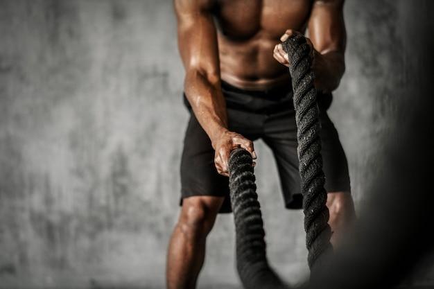 Muskularny mężczyzna ćwiczący na linach bojowych na siłowni