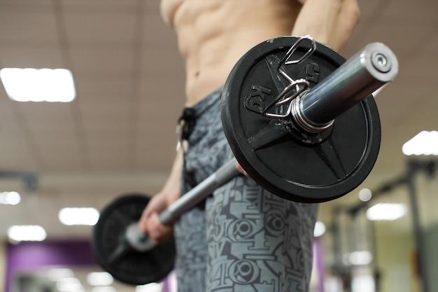 Muskularny mężczyzna ćwiczący na siłowni wykonujący ćwiczenia ze sztangą, silny mężczyzna nagi tors abs