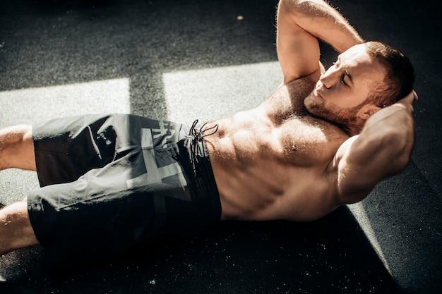 Muskularny mężczyzna ćwiczeń robi siedzieć ćwiczenia