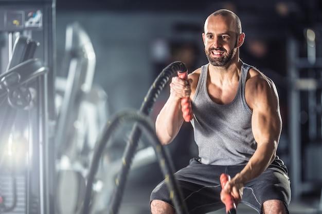 Muskularny mężczyzna ćwiczenia z lin bojowych na siłowni fitness.