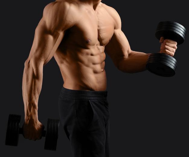 Muskularny mężczyzna ćwiczy z hantlami, pokazując swój idealny seksowny tors