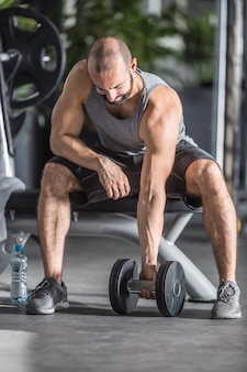 Muskularny mężczyzna ćwiczy z hantlami w siłowni.