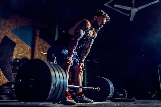 Muskularny mężczyzna fitness przygotowuje się do martwego ciągu sztangą w nowoczesnym centrum fitness.